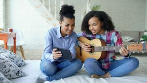 Young women with tablet and guitar
